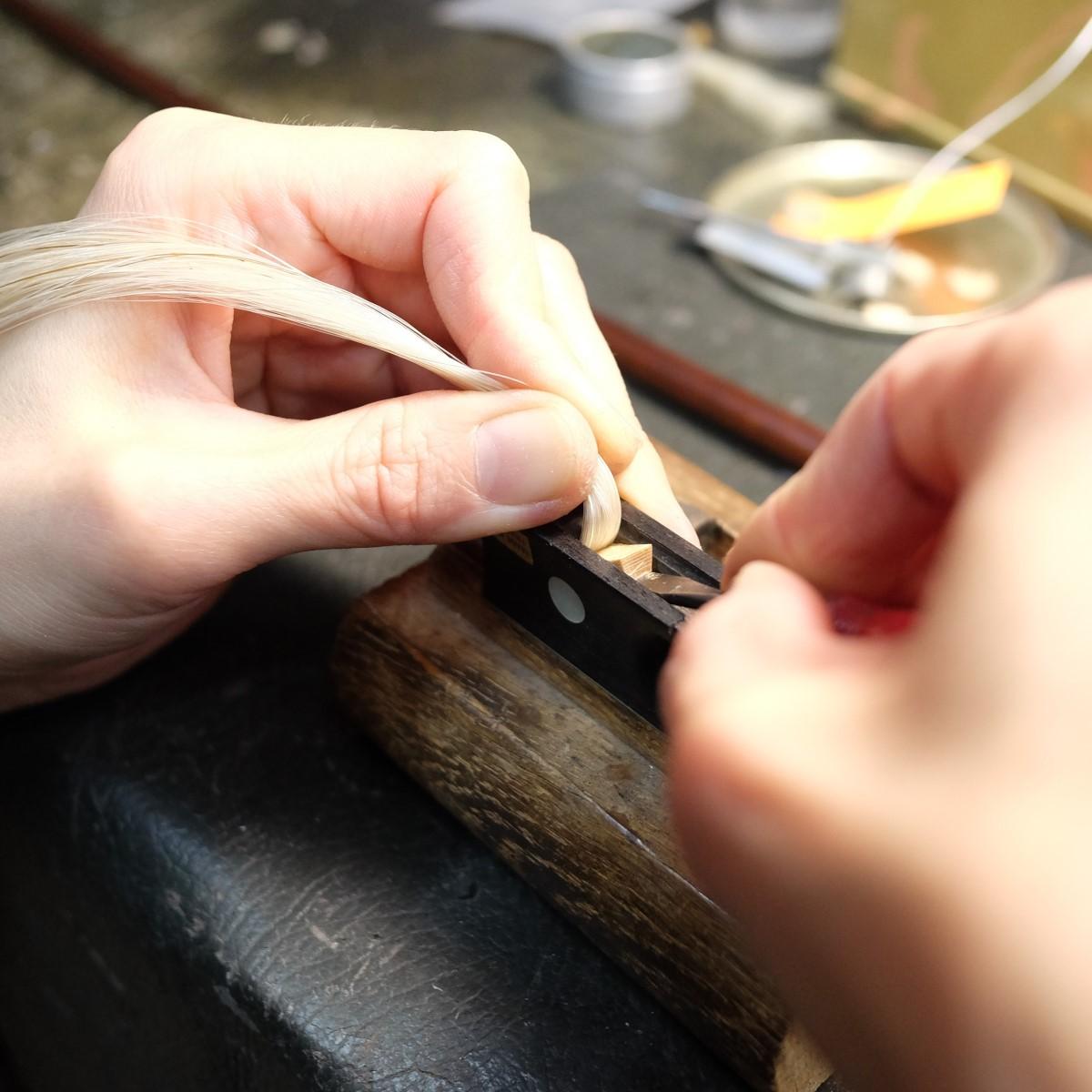 職人が弓の毛替えをしている手元