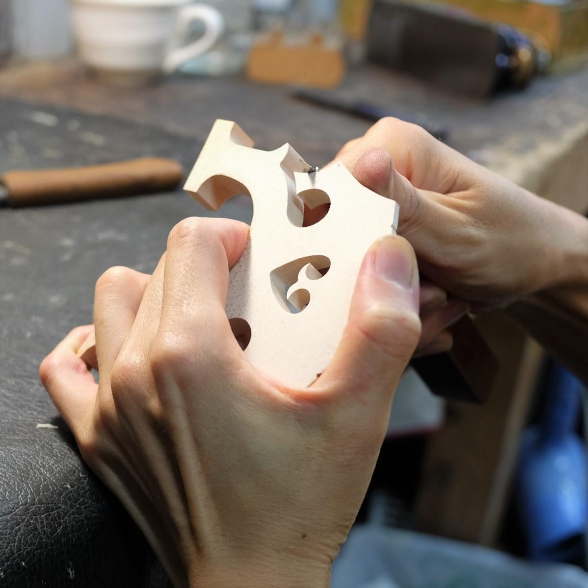 職人がチェロの駒を整形している手元