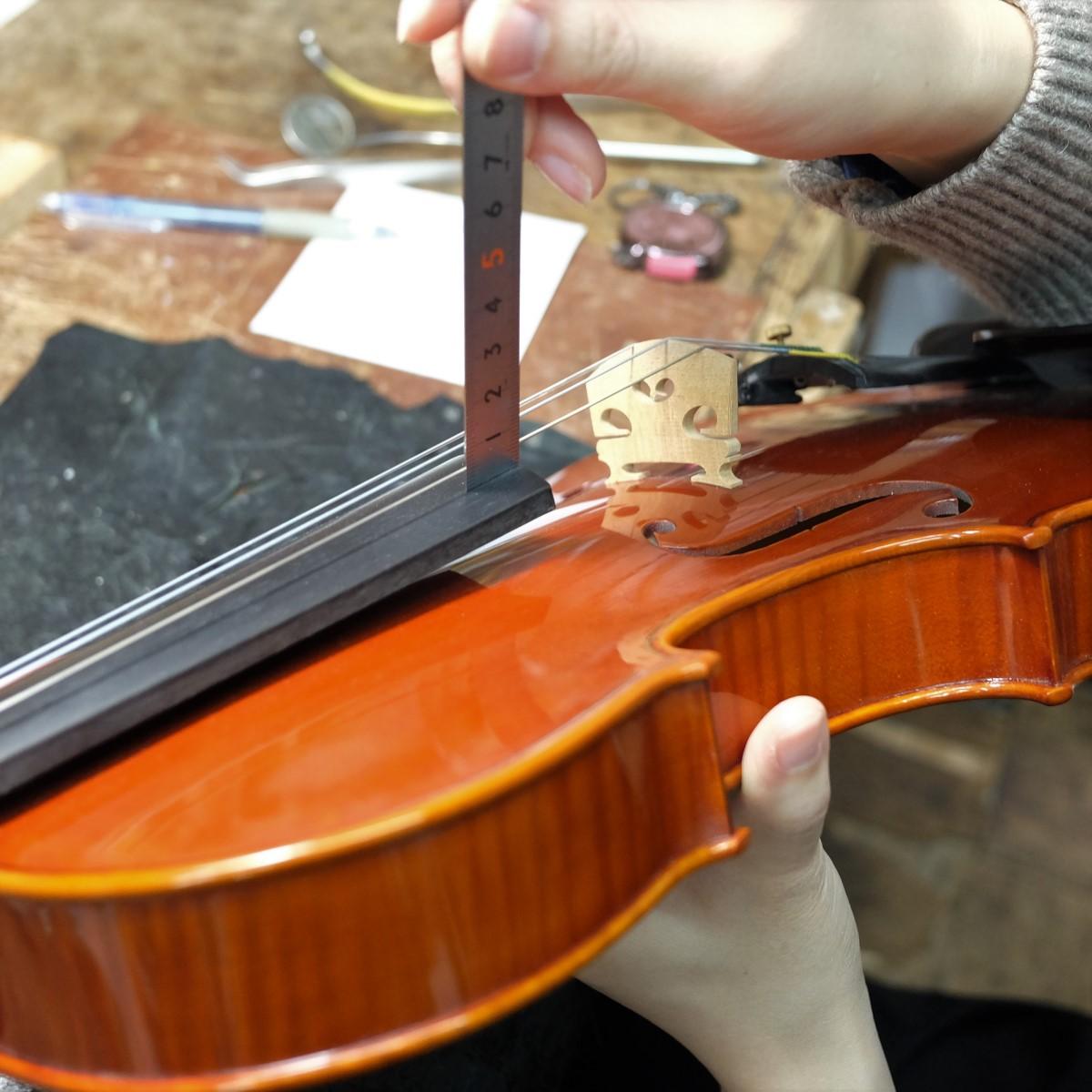 職人がバイオリンの点検を行っている手元