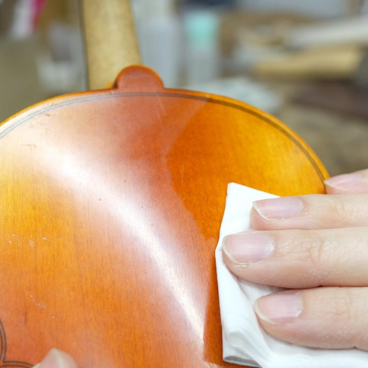 職人がバイオリンのクリーニングをしている手元