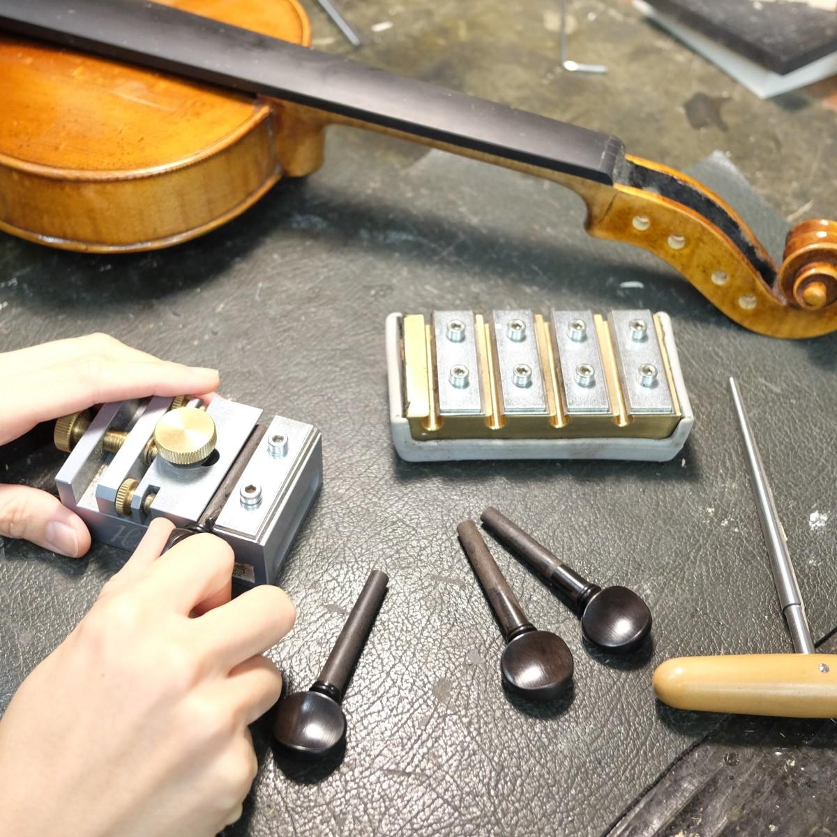 職人がバイオリンのペグの交換をしている手元