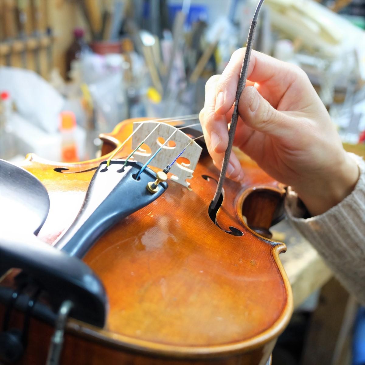 職人がバイオリンの魂柱を調整している手元