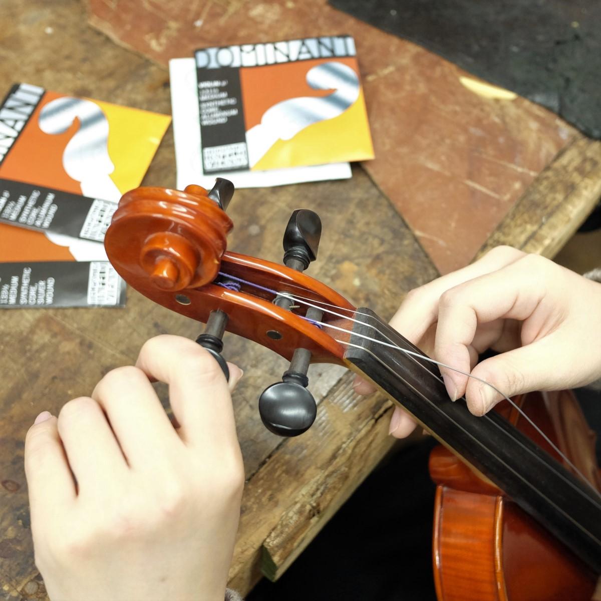 職人がバイオリンの弦交換をしている手元