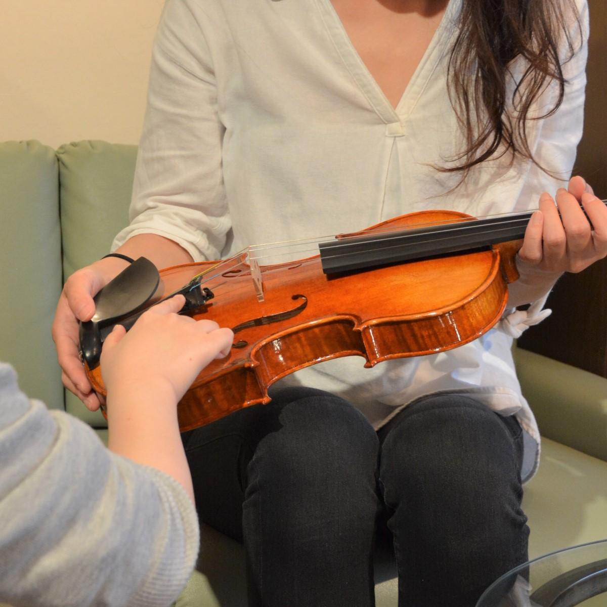 バイオリンの点検内容をお客様へ伝えている場面