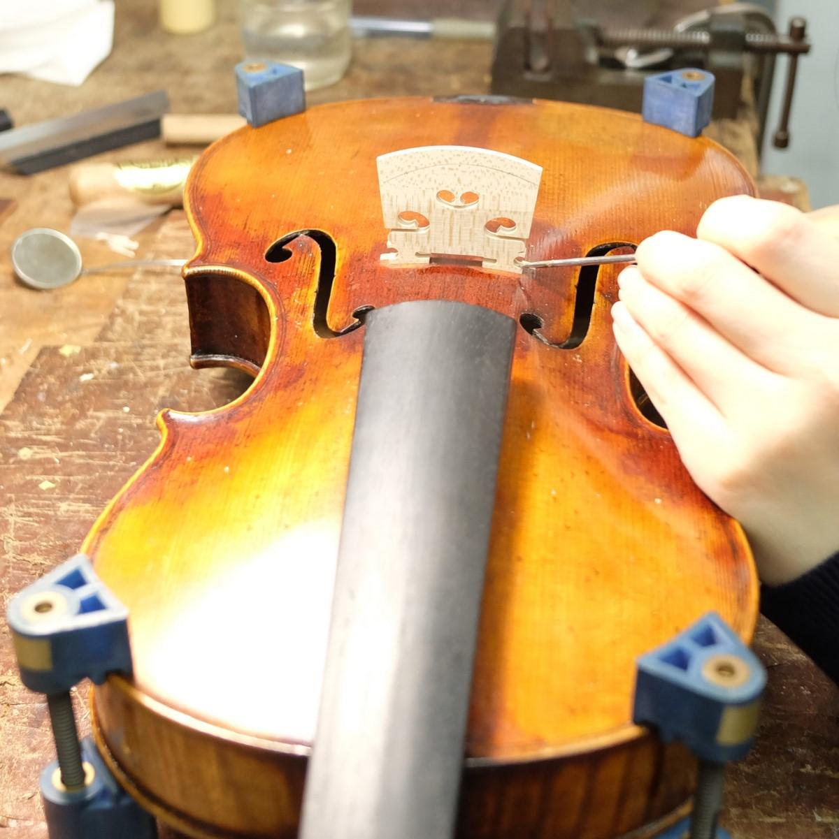職人がバイオリンの駒を交換している手元
